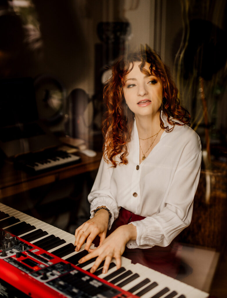 Redheaded woman - singer and voice teacher Aleksandra - singing and playing a red Nord Piano.